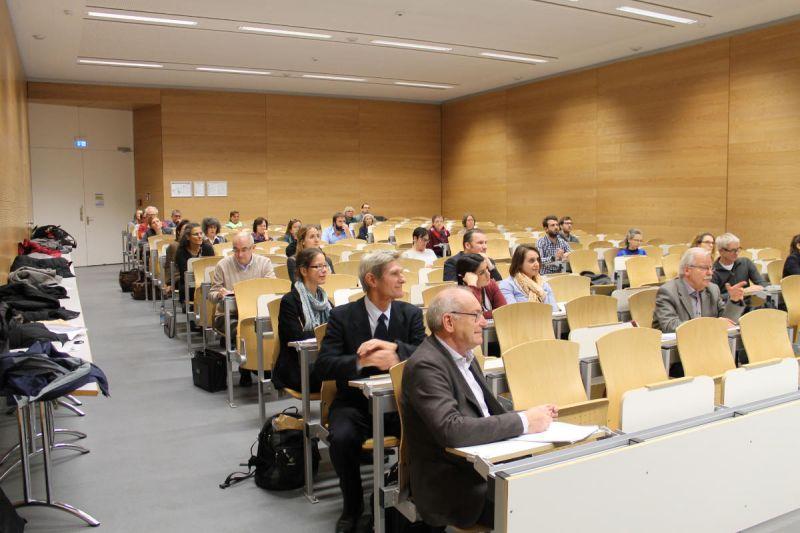 Teilnehmer sitzen im Hörsaal und hören einem Vortrag zu.