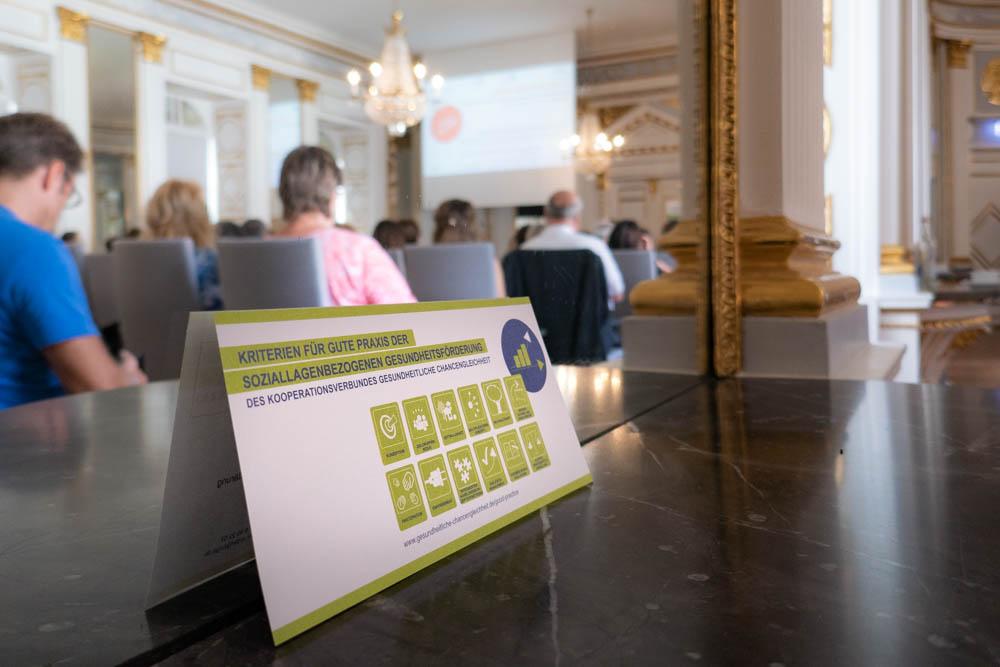 Foto von Vortragssaal mit Teilnehmern des Fachforums und Flyer für Gute Praxis