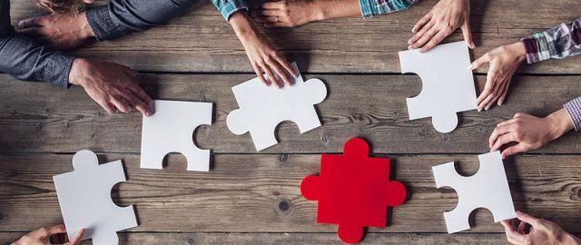 Hände setzen große Puzzlestücke auf Tisch zusammen